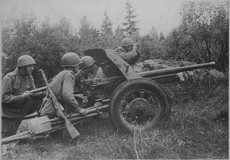Замполит смотрит в бинокль возле пушки ВОВ