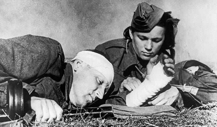 Женщина санитарка перебинтовывает солдата