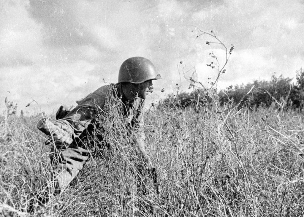Солдат с гранатой идет по полю ВОВ